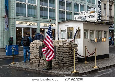 Berlin, Germany - April 19, 2017: Men Wearing American Military Uniforms Stand At The Famous Checkpo