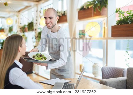 Waiter serving the businesswoman during business lunch