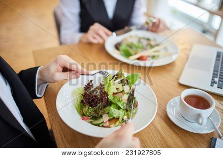 Close-up of business people eating salad at restaurant