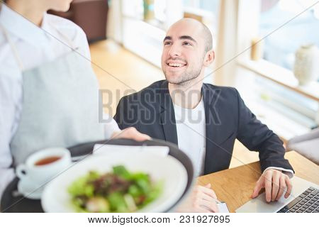 Smiling man using his laptop at restaurant