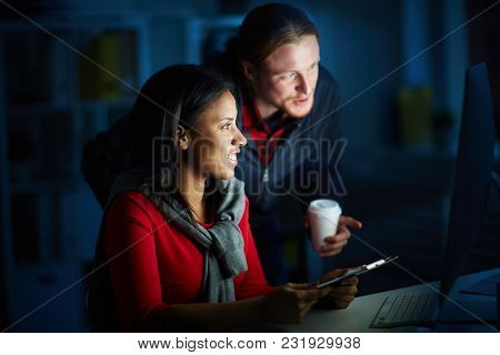 Businesspeople working in team till night. They are using computer for work