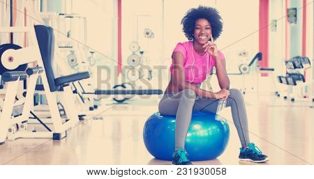 young Athletic healthy black woman resting during workout in gym