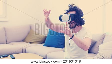 happy man getting experience using VR-headset glasses of virtual reality at home