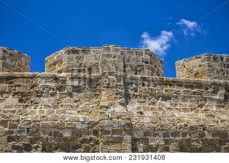Ancient Stone Wall Close-up Against A Blue Sky.  Medieval Fortress: Part Of The Fortification  . Cit
