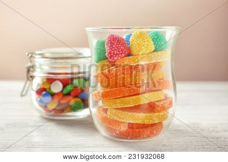 Glassware with colorful candies on table against light background