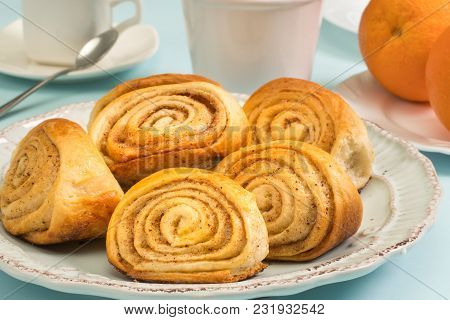 A Cup Of Tea And Pastries. Buns With Cinnamon And Orange. Morning Breakfast On A Plate. A Cup Of Tea