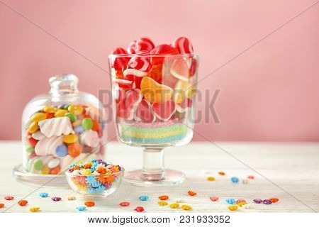 Glassware with sprinkles and different candies on table against color background