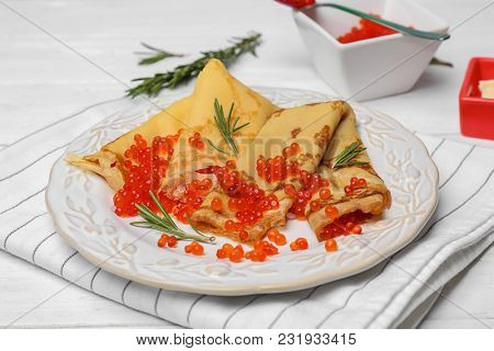 Plate with thin pancakes and red caviar on table