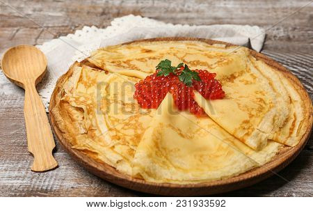 Plate with thin pancakes and red caviar on wooden table, closeup