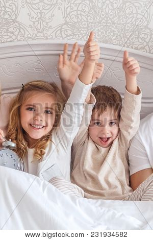 Happy Kids Relaxing In Bed Together In Morning And Showing Thumbs Up