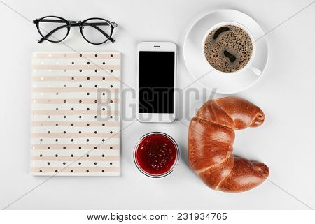 Composition with fresh tasty crescent roll, coffee and mobile phone on white background, flat lay