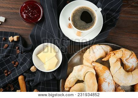 Composition with fresh tasty crescent rolls and coffee on wooden table