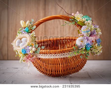 Beautiful Decorative Basket With Flowers To Celebrate Easter On Wooden Board