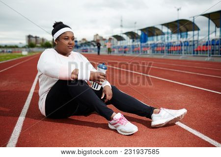 Young restful woman sitting on race track and refreshing with water after training