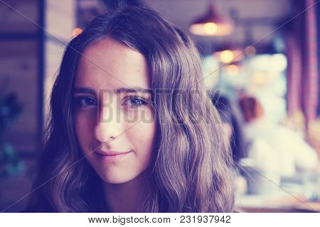 Cute Looking Girl In A Cafe. With Big Brown Beautiful Eyes. With Nice Brown Long Hair. Wearing A Bro