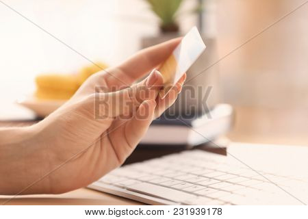Woman holding credit card near computer, closeup