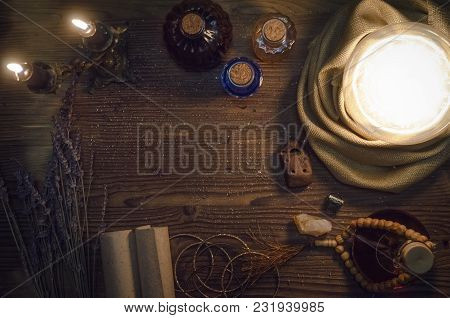 Crystal Ball And Ancient Magic Scrolls On Fortune Teller Magic Desk Table Background. Seance Concept