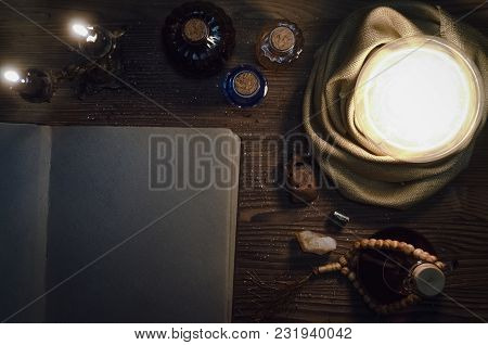 Crystal Ball And Open Magic Book With Blank Pages On Fortune Teller Magic Desk Table Background. Sea