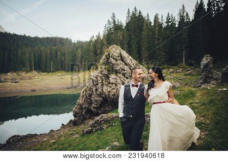 Stylish Couple Of Newlyweds Against The Backdrop Of The Mountains In Italy