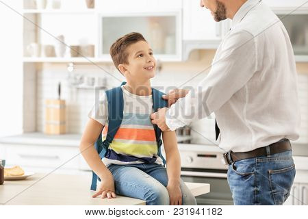 Man helping his son get ready for school