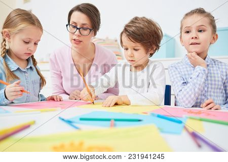 Three cute kids with teacher sitting by table and learning to draw with crayons in elementary school