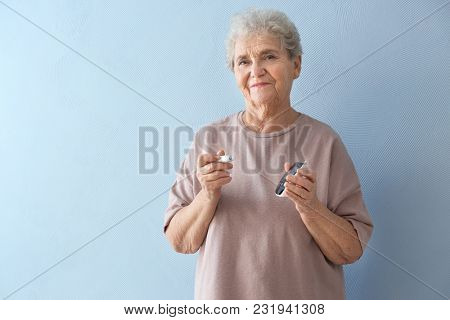 Elderly diabetic woman with lancet pen and glucometer on color background