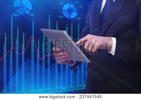 Businessman Using Tablet On Abstract Blue Forex Chart Background. Investment And Analysis Concept