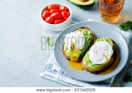 Poached Egg Avocado Rye Toasts On A Stone Background