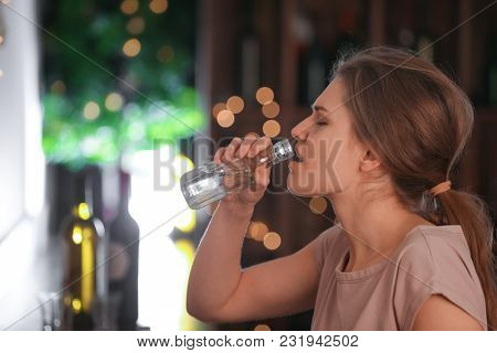 Young woman drinking in bar. Alcoholism problem