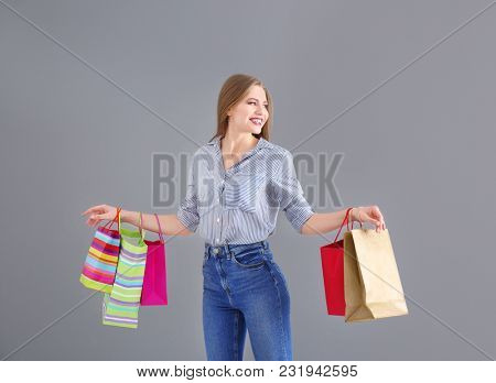 Beautiful young woman with shopping bags on grey background