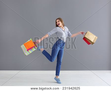 Beautiful young woman with shopping bags against grey wall