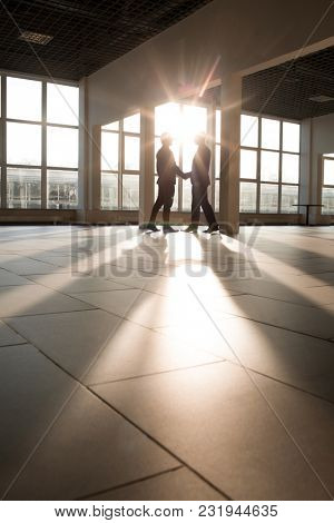 Two business partners shaking hands against window of working area in modern building
