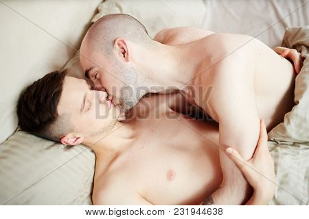 Amorous gay guy kissing and cuddling his lover while relaxing in bed