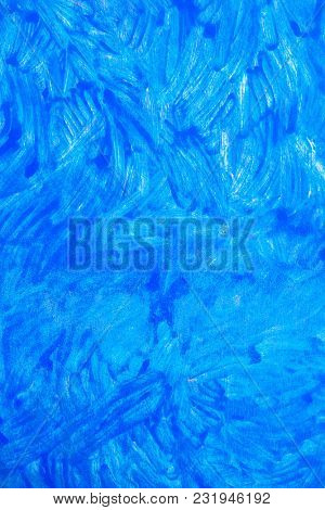 Bright blue paint applied with random brush strokes. Artistic paint background.