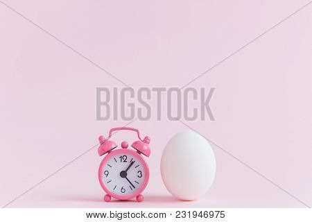 Small Alarm Clock And White Egg On Pastel Pink Background. Eastertime Minimal Concept.