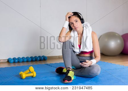 Girl tired after workout sitting on mat and listening to music in headphones in gym