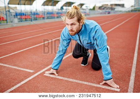 Young determined man in sportswear standing by start line on race track