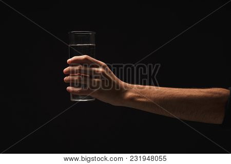 Male Hand Holding Glass Of Water Isolated On Black Background, Closeup, Cutout, Copy Space