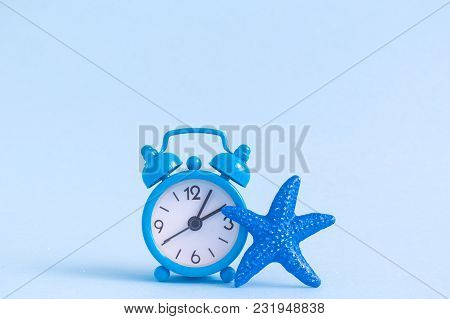 Alarm Clock And Starfish Against Pastel Blue Background. Summertime Minimal Concept.