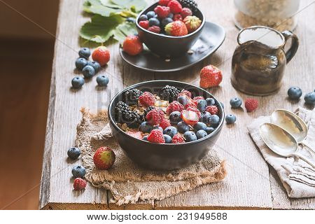 Delicious Homemade Granola Or Oatmeal With Berries For Breakfast Over Rustic Wooden Background