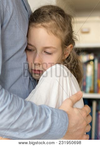 Sad Little Girl Hugging Her Dad At Home.
