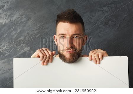 Handsome Serious Man Posing And Holding White Pape With Copy Space For Commercial Advertising At Gra