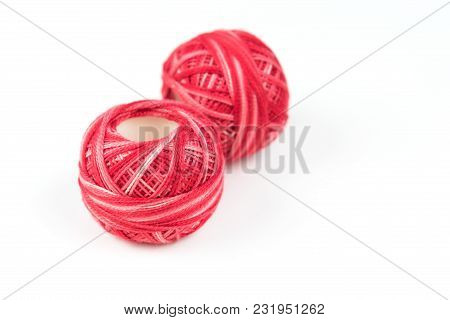 Two Red Sewing Threads On A White Background