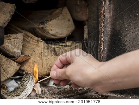 Kindling Firewood With A Match In The Old Homemade, Brick Russian Oven. It Is Used For Heat And Cook