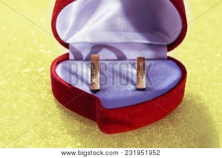 Wedding Rings Of Yellow Metal In A Beautiful Red Gift Box On A Snowy Yellow Surface