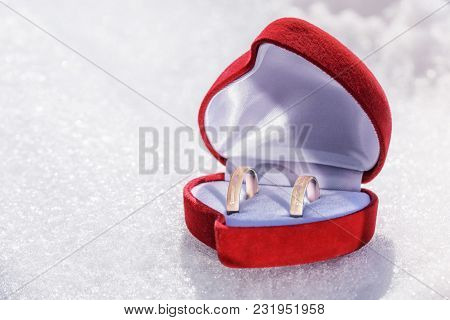 Wedding Rings Of Yellow Metal In A Beautiful Red Gift Box On A Snowy White Surface