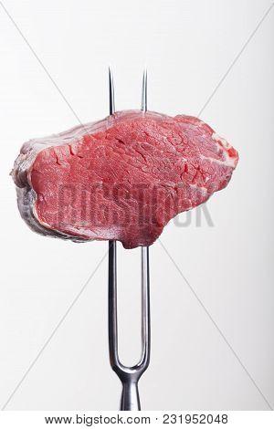 Steak On A Meat Fork On Grey