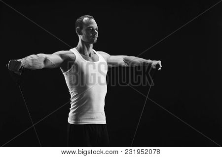 Sporty Muscular Man Exercising With Elastic Expander, Black And White Image, Low Key, Copy Space