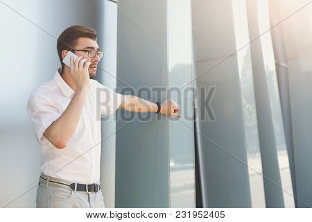 Attractive Thoughtful Businessman Or Lawyer In Eyeglasses Is Talking On Cell Phone Outdoors. Man Is