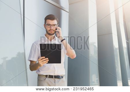 Attractive Pensive Businessman In Eyeglasses Is Holding Clipboard And Talking On Mobile Phone While